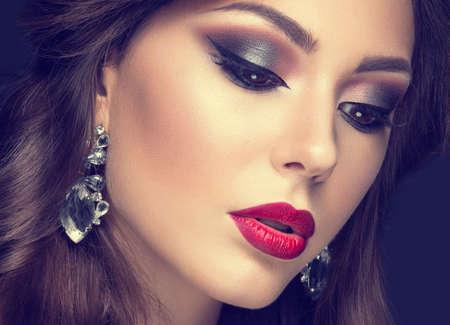 cruz roja: Mujer hermosa con maquillaje árabe, labios rojos y rizos. Cara de la belleza. Fotografía tomada en el estudio sobre un fondo gris. Foto de archivo