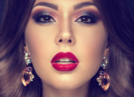beauté: Belle femme avec arabique maquillage, les lèvres rouges et boucles. Beauté visage. Photo prise dans le studio sur un fond gris.