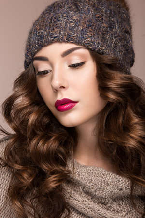 knit cap: Beautiful girl with a gentle make-up, curls  in winter brown knit cap. Warm winter image. Beauty face. Picture taken in the studio. Stock Photo