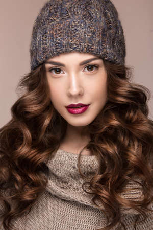 photo of accessories: Beautiful girl with a gentle make-up, curls  in winter brown knit cap. Warm winter image. Beauty face. Picture taken in the studio. Stock Photo