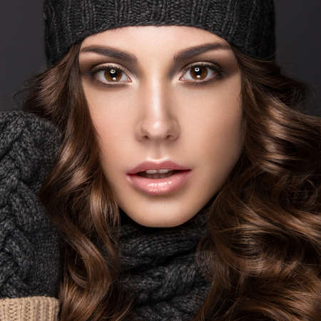 スモーキー化粧で美しい少女はカールの冬黒ニット キャップ。暖かい冬のイメージ。美容顔。スタジオでの撮影。