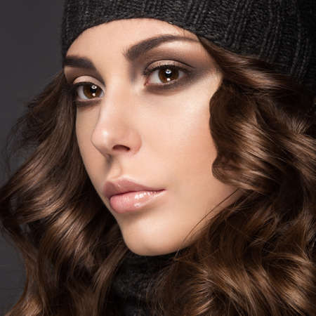 knit cap: Beautiful girl with a Smokey make-up, curls  in winter black knit cap. Warm winter image. Beauty face. Picture taken in the studio.