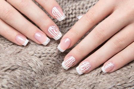 Snow White manicure op vrouwelijke handen. Winter nail design. Foto genomen in de studio op een achtergrond van wol.