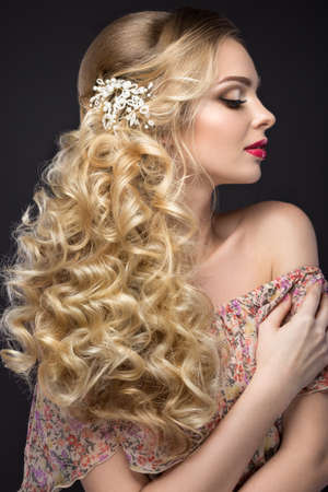 hair studio: Portrait of a beautiful blond girl in image of the bride with Wedding accessories on her head. Beauty face. Photo shot in the Studio on a grey background
