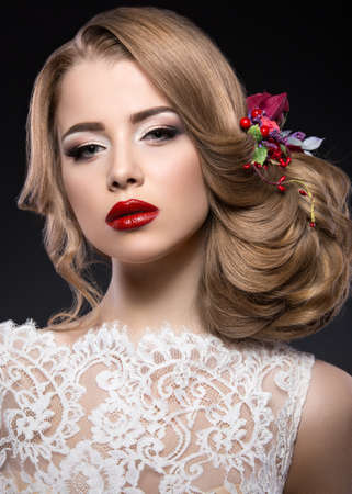 cola mujer: Retrato de una hermosa chica rubia en la imagen de la novia con flores de color púrpura en la cabeza. Cara de la belleza. Foto tirada en el estudio sobre un fondo gris