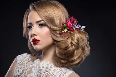 moda: Retrato de uma menina loura bonita na imagem da noiva com flores roxas na cabeça. Face da beleza. Foto disparada no estúdio em um fundo cinzento