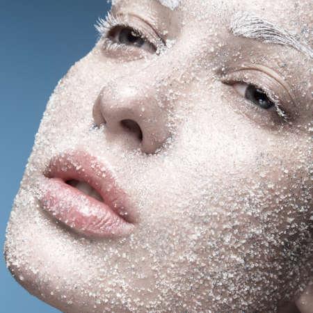 Portrait d'une jeune fille à la peau pâle et la neige de sucre sur son visage. Creative art mode beauté. Photo prise dans le studio sur un fond bleu. Banque d'images - 46801015
