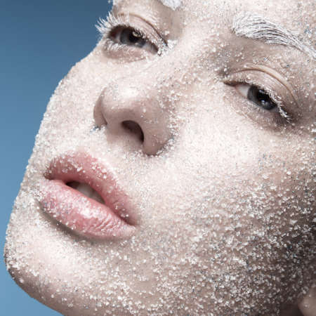 Portrait of a girl with pale skin and sugar snow on her face. Creative art beauty fashion. Picture taken in the studio on a blue background. Stockfoto