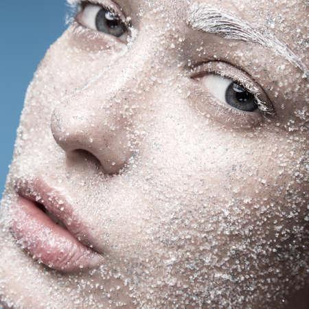 彼女の顔に青白い肌と砂糖雪の少女の肖像画。創造的な芸術美容ファッション。青色の背景のスタジオでの撮影。