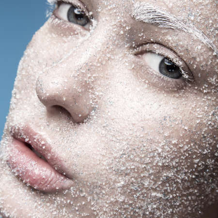 Portrait of a girl with pale skin and sugar snow on her face. Creative art beauty fashion. Picture taken in the studio on a blue background. Standard-Bild