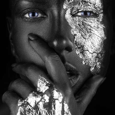 black girl nude: fashion portrait of a dark-skinned girl with silver foil make-up.Beauty face. Picture taken in the studio on a black background.