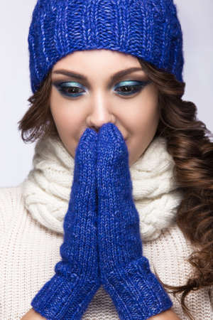 knit cap: Beautiful girl with a gentle make-up, curls and a smile in winter blue  knit cap. Warm winter image. Beauty face. Picture taken in the studio. Stock Photo