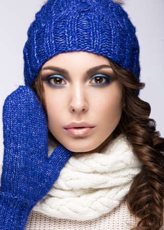 winter fashion: Beautiful girl with a gentle make-up, curls and a smile in winter blue  knit cap. Warm winter image. Beauty face. Picture taken in the studio. Stock Photo