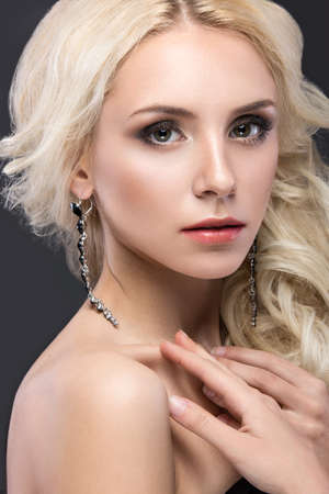 photo of accessories: Beautiful blond woman with evening make-up, tender lips and curls. Beauty face. Picture taken in the studio on a gray background