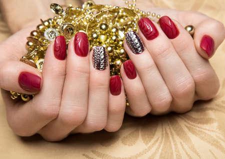 女性の手にクリスタルの美しい赤のマニキュア。クローズ アップ。スタジオでの撮影