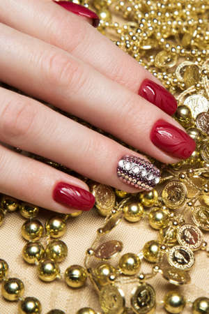 short order: Beautiful red manicure with crystals on female hand. Close-up. Picture taken in the studio
