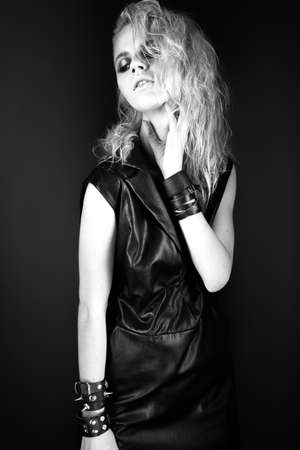 daring: Daring girl model in black leather dress in the style of rock, dark make-up, wet hair and bracelets on her arms. Picture taken in the studio. Black-and-white image.