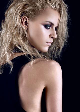daring: Daring girl model in black dress in the style of rock, dark make-up, wet hair. Picture taken in the studio. Stock Photo