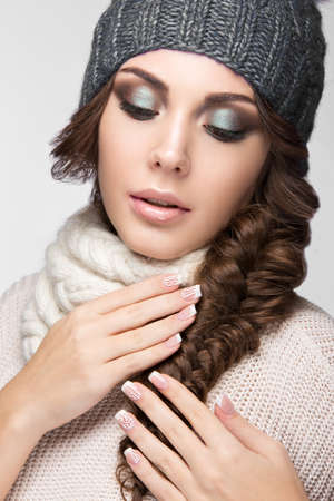 knit cap: Beautiful girl with a gentle make-up, design manicure and winter gray knit cap. Warm winter image. Beauty face. Picture taken in the studio. Stock Photo
