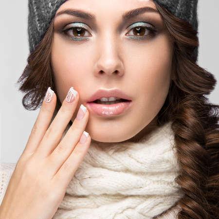 穏やかなメイクで美しい少女は、デザインのマニキュアと冬の灰色ニット キャップです。暖かい冬のイメージ。美容顔。スタジオでの撮影。