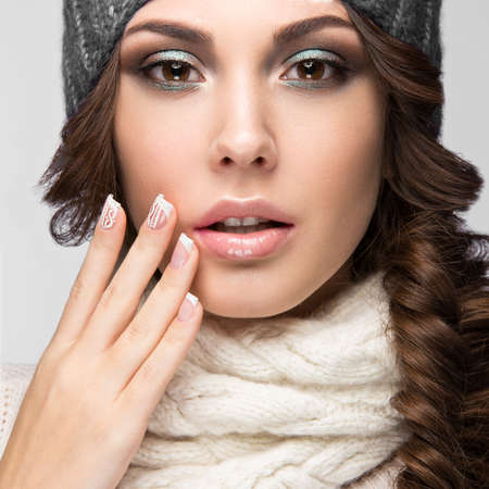Beautiful girl with a gentle make-up, design manicure and winter gray knit cap. Warm winter image. Beauty face. Picture taken in the studio. Standard-Bild