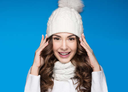 white  hat: Beautiful girl with a gentle make-up, design manicure and a smile in winter white knit cap. Warm winter image. Beauty face. Picture taken in the studio.