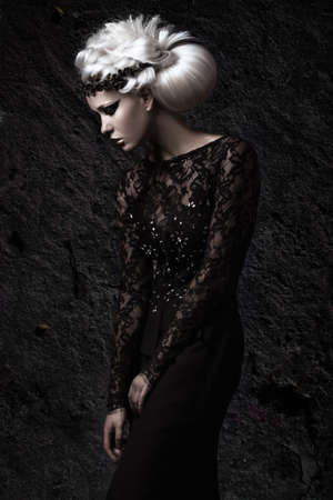 glamour woman: Beautiful girl in gloomy image with a white wig, unusual hairstyle, black dress and dark makeup. Art beauty, fashion model. Picture taken in the studio.
