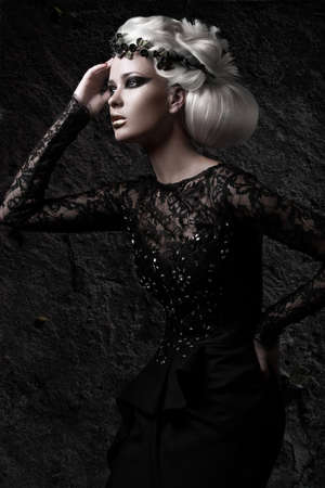 Beautiful girl in gloomy image with a white wig, unusual hairstyle, black dress and dark makeup. Art beauty, fashion model. Picture taken in the studio.