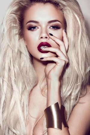 labios sensuales: Hermosa chica rubia sexy con labios sensuales, el pelo, las u�as negras de moda y accesorios de oro. Cara de la belleza. Imagen tomada en el estudio Foto de archivo