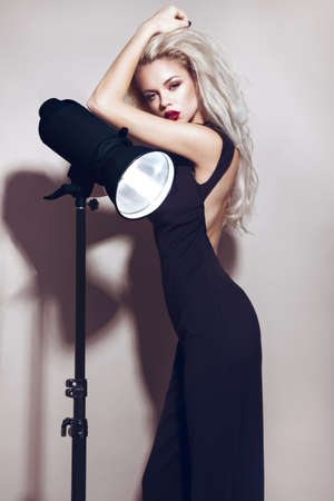 Beautiful sexy blonde girl with sensual lips, fashion hair, black dress and gold accessories. Beauty face. Picture taken in the studio