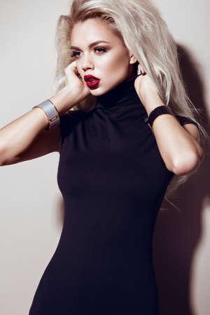 Hermosa chica rubia sexy con labios sensuales, pelo de la manera, vestido de negro y accesorios de oro. Cara de la belleza. Imagen tomada en el estudio