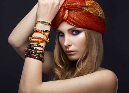 Beautiful fashion girl in a scarf and bracelets boho style. Beauty face, bright trendy makeup. Picture taken in the studio. Standard-Bild