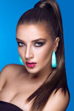 sexy young girl: Красивая женщина с вечерний макияж, яркие аксессуары и длинные прямые волосы. Дымчатый глаз. Мода фото. Снимок сделан в студии на синем фоне. Фото со стока