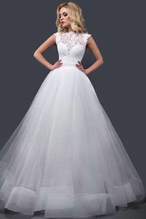 mujeres fashion: Hermosa mujer rubia en vestido de novia con maquillaje de la tarde, los labios tiernos y rizos. imagen Novia. Cara de la belleza. Fotograf�a tomada en el estudio sobre un fondo gris Foto de archivo