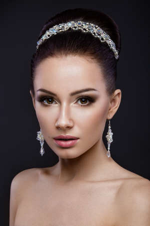 nude bride: Beautiful brunette girl with perfect skin, evening make-up, wedding hairstyle and accessories.Beauty face. Picture taken in the studio. Stock Photo