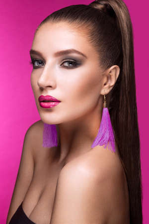 makeup eyes: Beautiful woman with evening make-up, bright accessories and long straight hair . Smoky eyes. Fashion photo. Picture taken in the studio on a pink background.