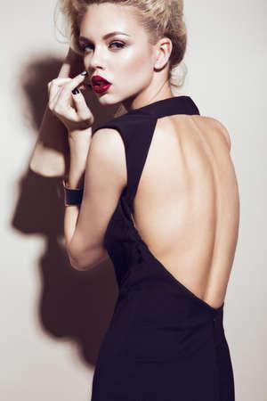 官能的な唇、ファッションの髪、黒いドレスとゴールドのアクセサリーで美しいセクシーなブロンドの女の子。美容顔。スタジオでの撮影