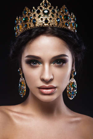 young style: Beautiful brunette girl with a golden crown and earrings and professional evening make-up. Beauty face. Picture taken in the studio.