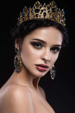 Beautiful brunette girl with a golden crown and earrings and professional evening make-up. Beauty face. Picture taken in the studio.
