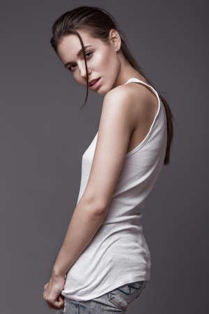jeune femme nue: mannequin sexy avec les cheveux longs, les jeunes attrayants, beaux yeux européens, une peau parfaite est posant en studio pour le glamour vogue photo de test tournage montrant différentes poses. Photo prise dans le studio sur un fond gris.