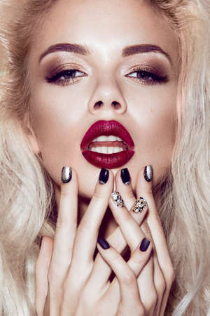 Beautiful blonde girl with sensual lips, fashion hair, black nails. Beauty face. Picture taken in the studio