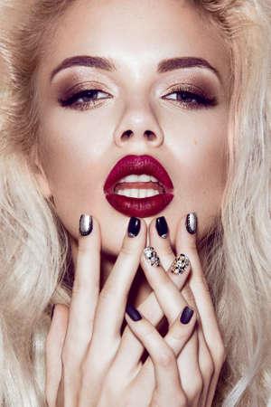 unas largas: Hermosa chica rubia atractiva con los labios sensuales, la moda del cabello, las uñas negras. Cara de la belleza. Imagen tomada en el estudio