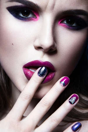 pink lips: Beautiful girl with bright creative fashion makeup and colorful nail polish. Art beauty design. Beauty face. Studio portrait Stock Photo