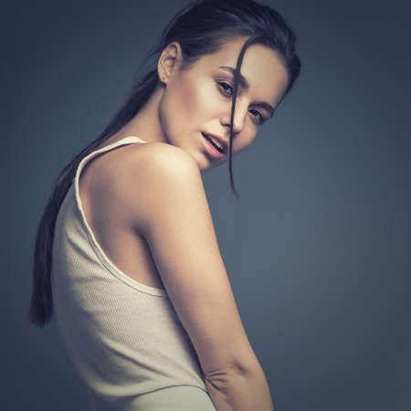 modelos desnudas: Modelo de manera atractivo con el pelo largo, j�venes atractivas, hermosos ojos europeos, piel perfecta est� presentando en estudio de moda glamour prueba sesi�n de fotos que muestra diferentes poses. Fotograf�a tomada en el estudio sobre un fondo gris.