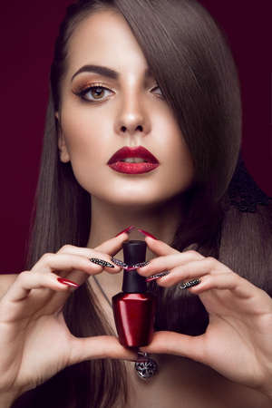 hair product: Pretty girl with unusual hairstyle, bright makeup, red lips and manicure design with a jar of nail polish in her hands. Beauty face. Art nails. Picture taken in the studio on a red background. Stock Photo