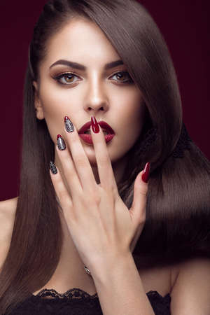 Pretty girl with unusual hairstyle, bright makeup, red lips and manicure design. Beauty face. Art nails. Picture taken in the studio on a red background. Stockfoto