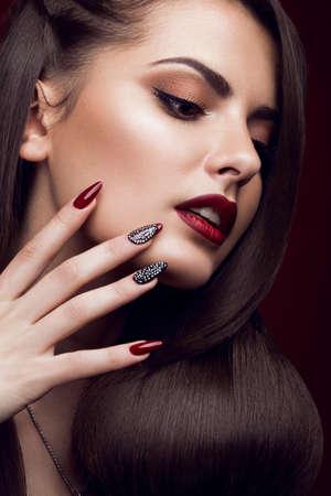 Hübsches Mädchen mit ungewöhnlichen Frisur, hellen Make-up, roten Lippen und Maniküre Design. Beauty Gesicht. Kunstnägel. Gemachtes Bild im Studio auf einem roten Hintergrund.