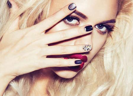 modelo desnuda: Hermosa chica rubia atractiva con los labios sensuales, la moda del cabello, las u�as negras. Cara de la belleza. Imagen tomada en el estudio