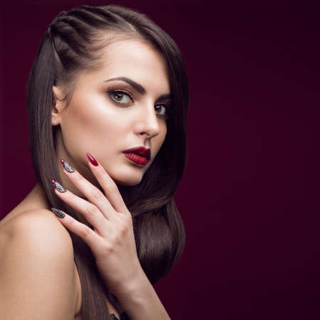 photo of accessories: Pretty girl with unusual hairstyle, bright makeup, red lips and manicure design. Beauty face. Art nails. Studio portrait Stock Photo