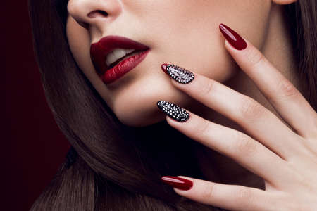 Pretty girl with unusual hairstyle, bright makeup, red lips and manicure design. Beauty face. Art nails. Studio portrait Imagens